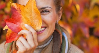 woman signifies changing seasons with autumn leaf
